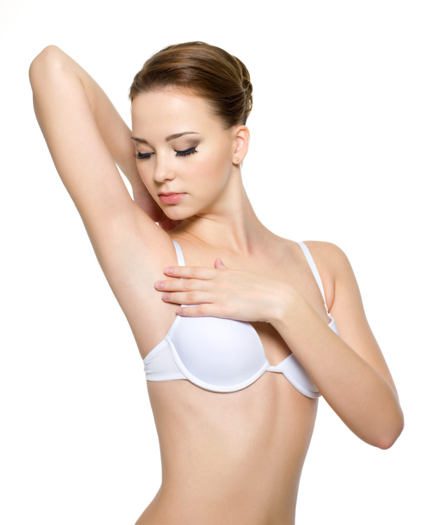 Female touching and looking on her clean armpit - isolated on white